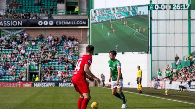 Hibs players in front of ADI LED screen